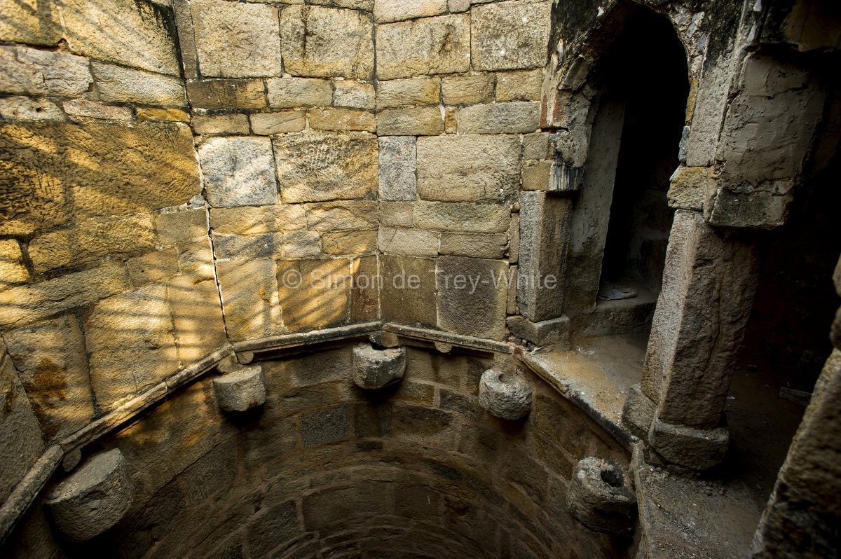 The well shaft of Rajon Ki Baoli in Mehrauli complete with stone rope-guides and grooved pillars above to take the ropes