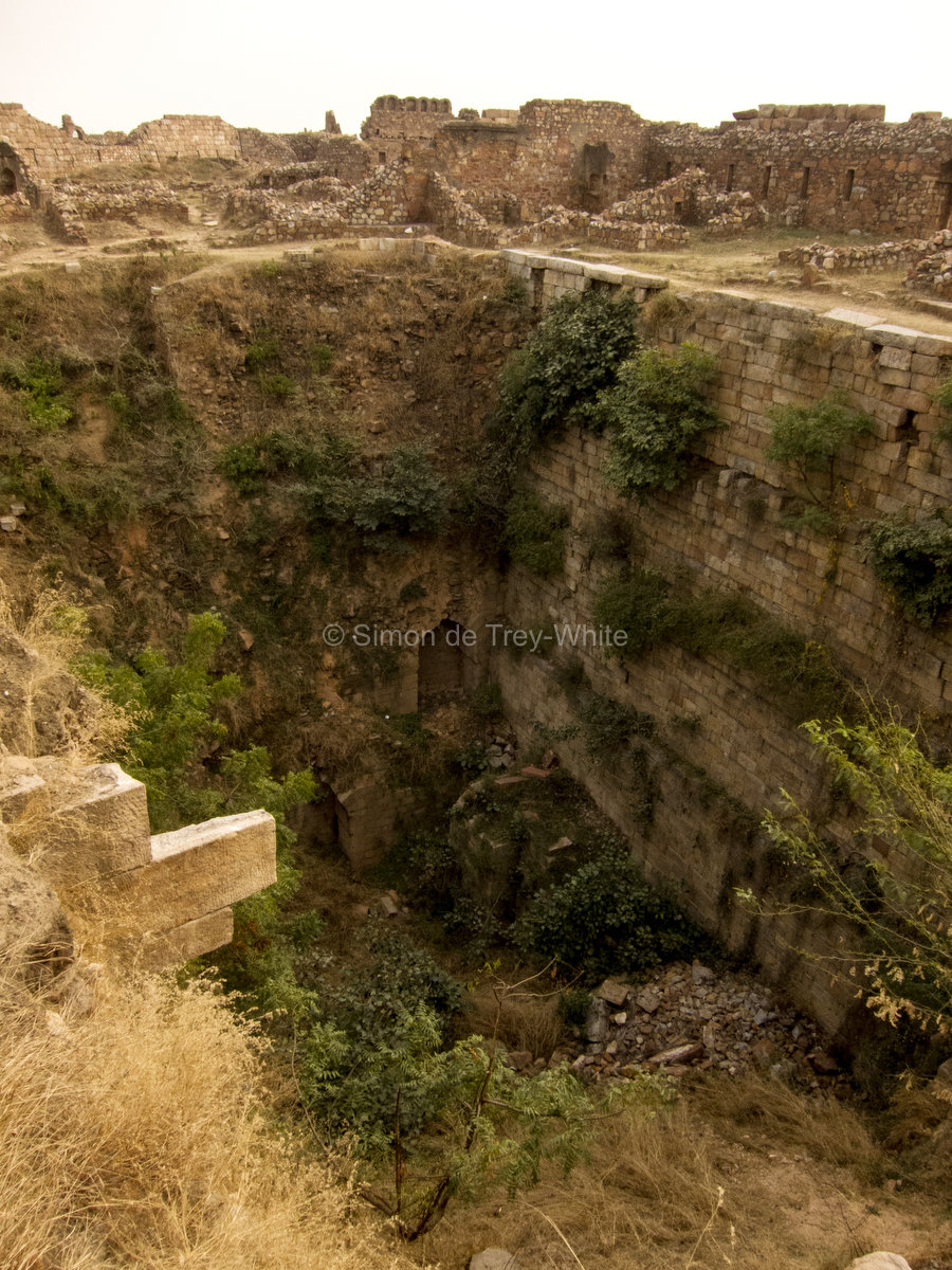 An overgrown and runied baoli within Tughlaqabad Fort