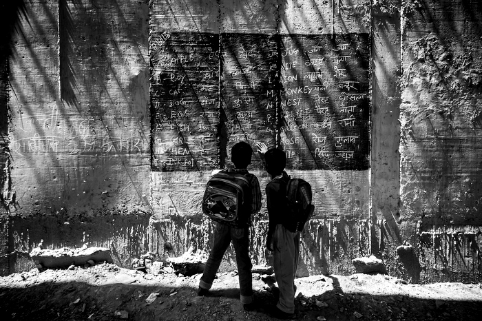 Boys read from a blackboard painted onto the wall of a metro bridge on the  8th of April 2013