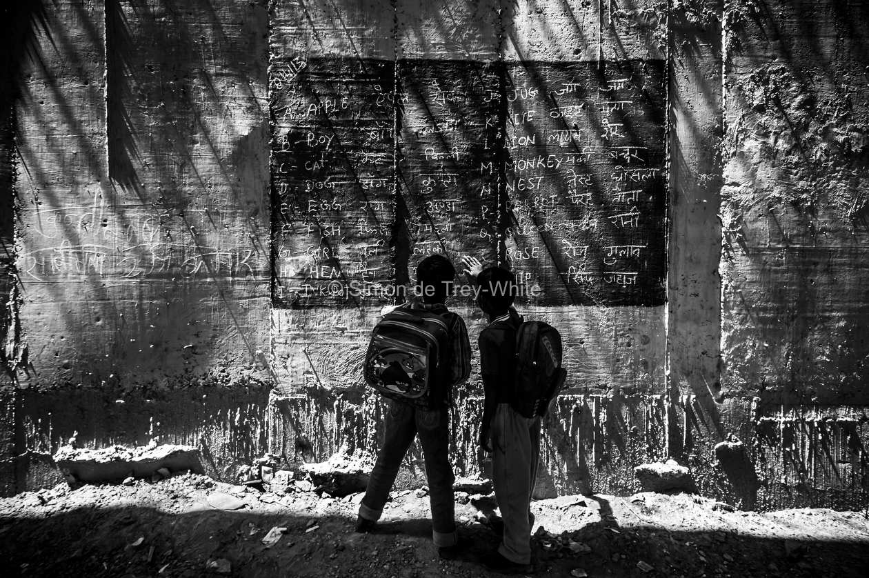 Boys read from a blackboard painted onto the walls of a metro bridge at a makeshift school in New Delhi, 8th April 2013