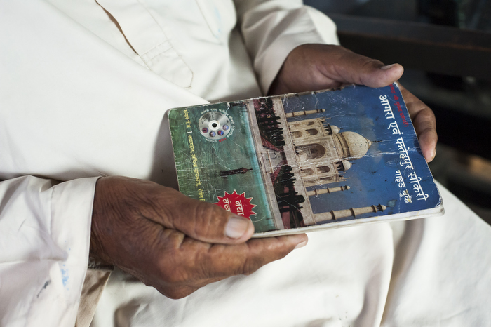 Mr Quadri, holds a pamphlet on the Taj Mahal that he used to design his replica monument