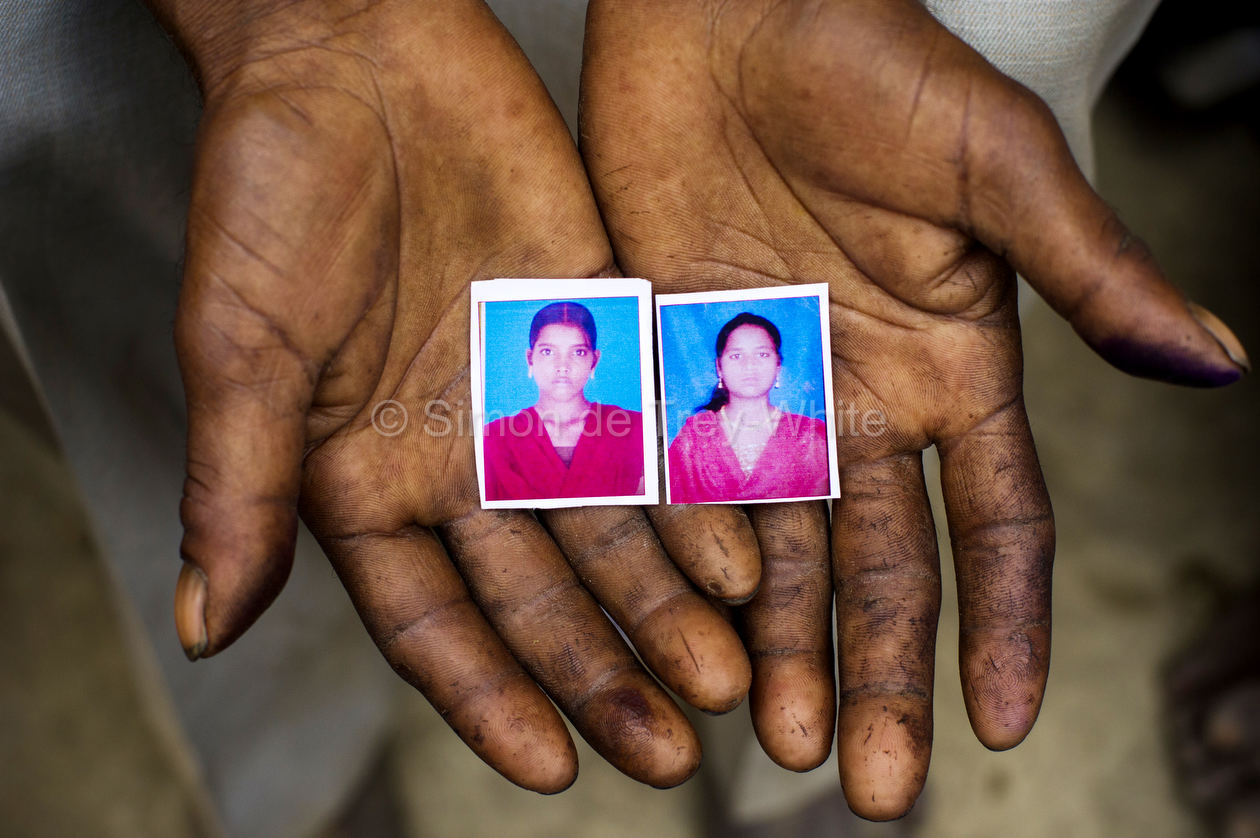 Labourer Sohan Lal (55) holds passport sized images of his daughter Murti (right) and niece Pushpa (left) in Katra Sadatganj village,Ushait near Baduan, Uttar Pradesh, India on the 30th May 2014.